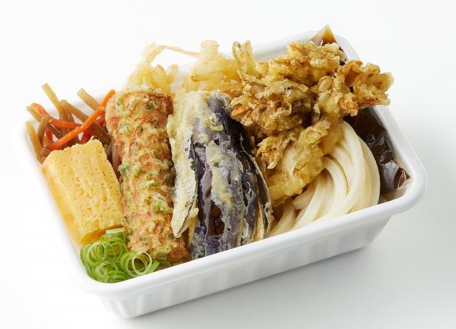 31日より登場する秋の新作『秋野菜の天ぷらと定番おかずのうどん弁当』(税込620円)の画像